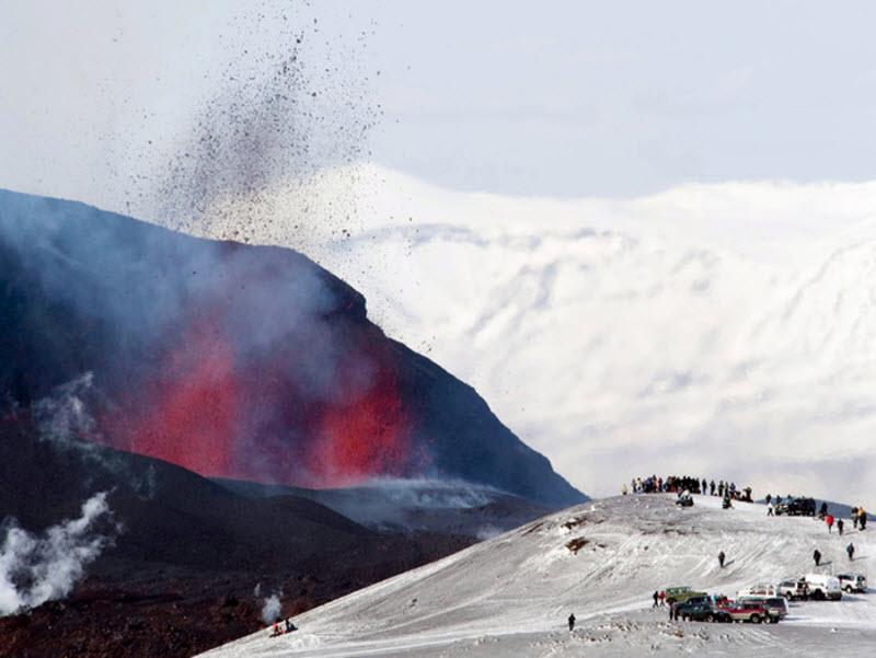 Туристы собрались посмотреть извержение вулкана Фиммвёрдюхаулс недалеко от ледника Эйяфьятлаёкюдль, в 128 км к востоку от столицы Исландии Рейкьявик